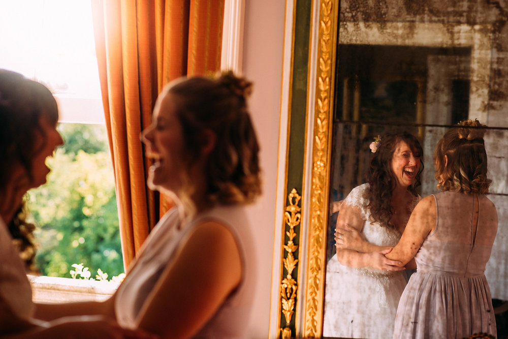 bride and bridesmaid laughing with reflection in the mirror