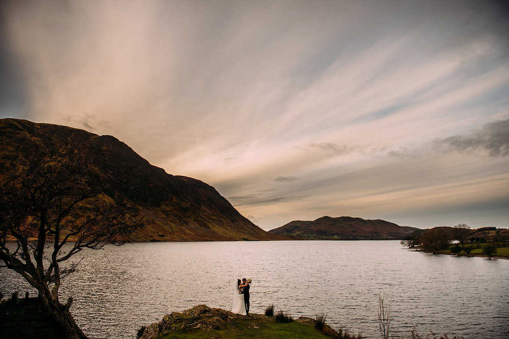 long distance shot of couple standing by Buttermere water in the lakes