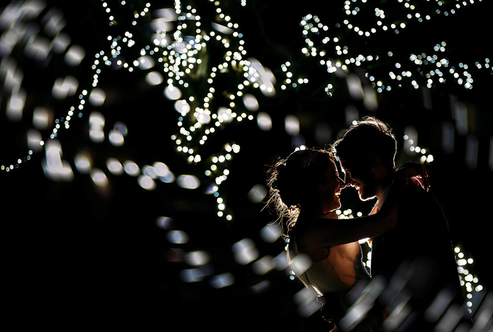 couple laughing in front of fairy lit tree at Stirk house