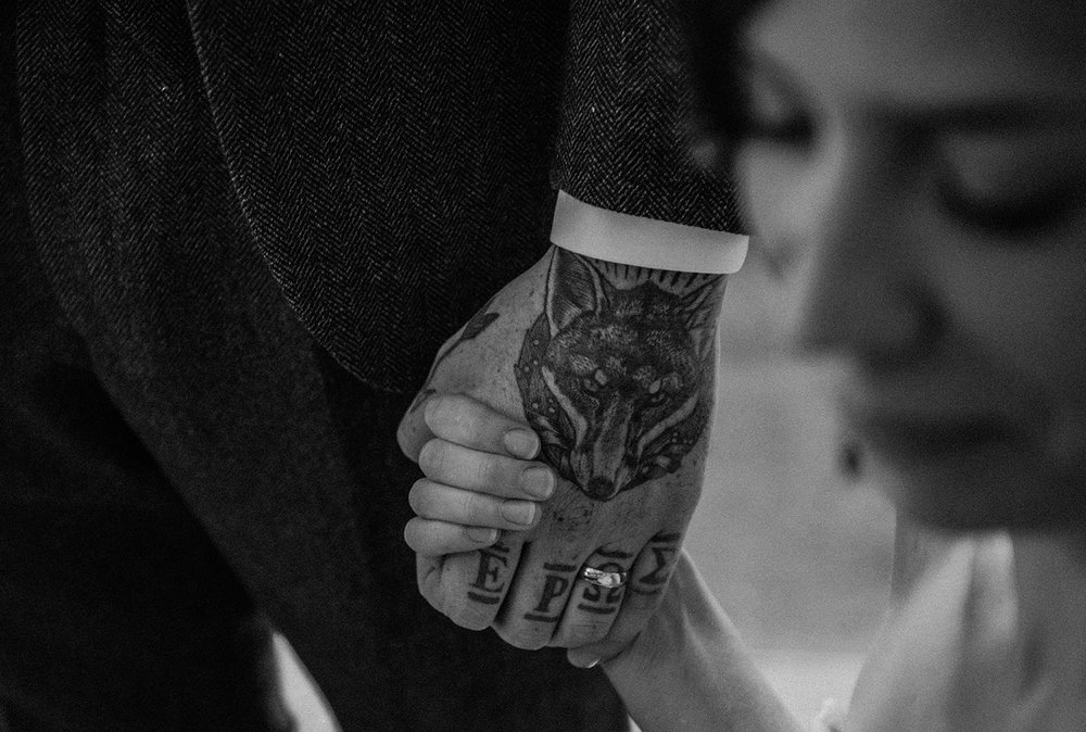 Black and white photo of bride holding grooms tattoo'd hand