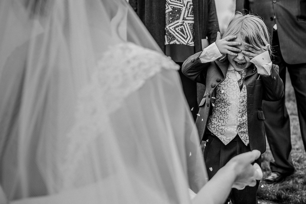 boy throwing confetti over himself in front of his mum - the bride