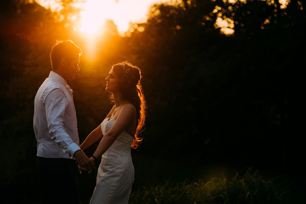 bride and groom holding hands and chatting at sunset