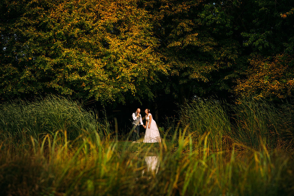 bride and groom laughing by a large pond
