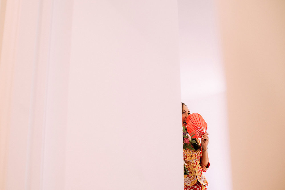 Chinese wedding, shot through a gap in the door of bride laughing behind her fan