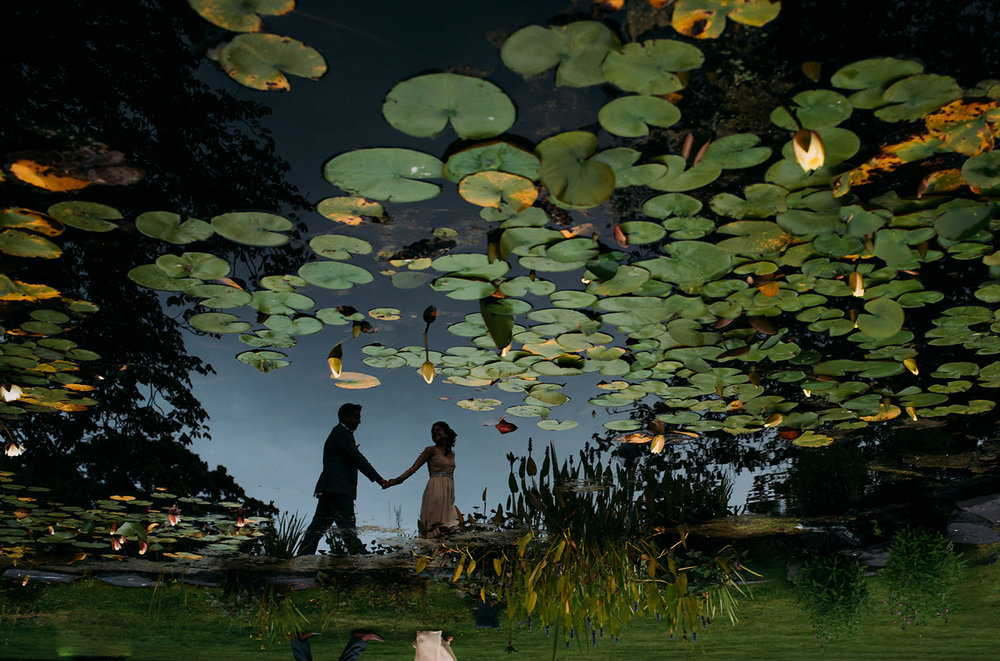 reflection of bride and groom in a pond filled with waterlillies
