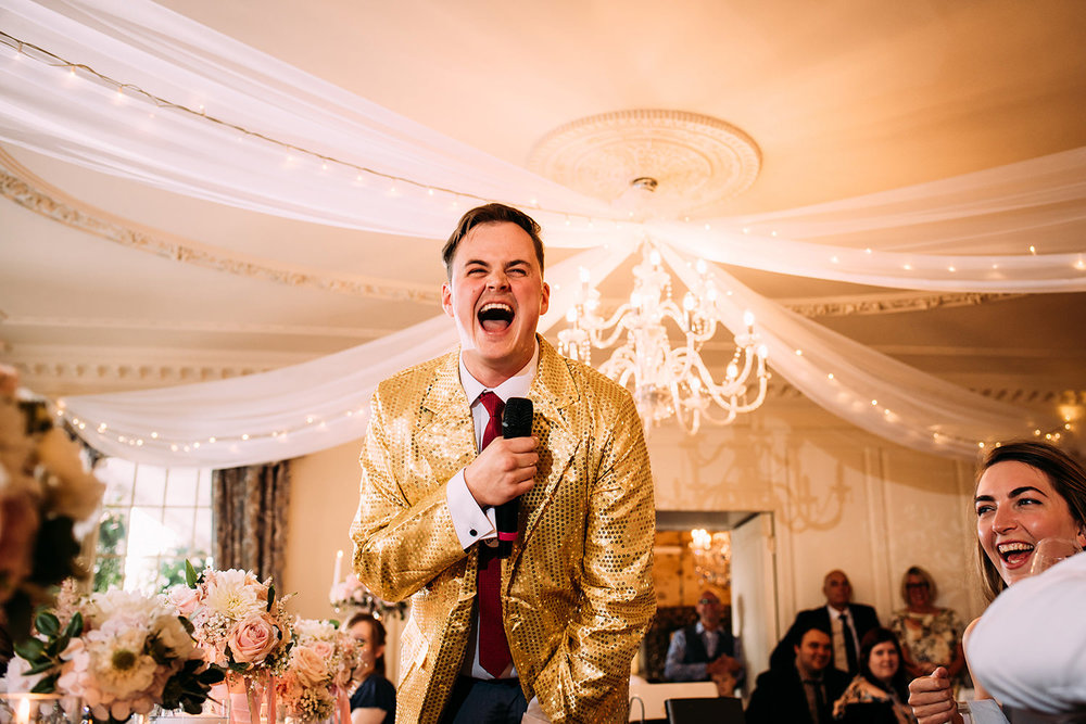 best man speech host in a glittery 'price is right' jacket, holding a microphone and laughing