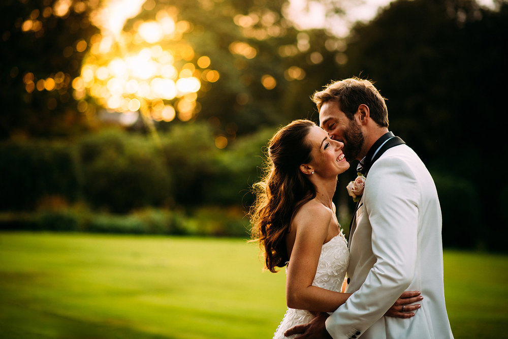 Bride and groom kissing and laughing in golden light at Eaves hall