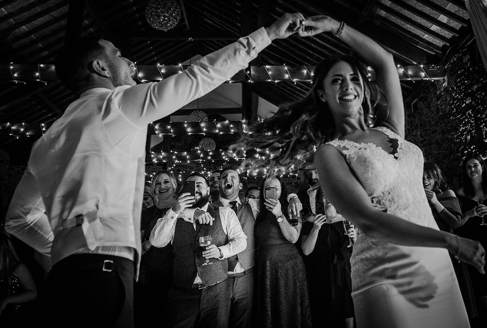Black and white photo of bride and groom spinning during the first dance - focus is on friends laughing in the background