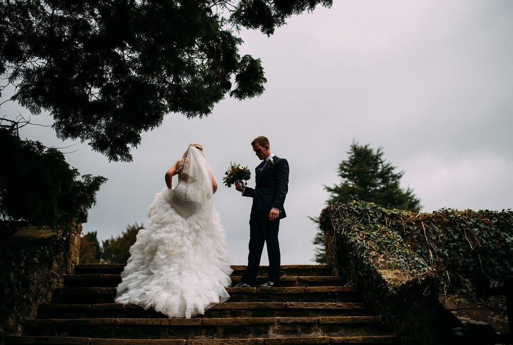 bride walks up steps in the grounds of Eaves hall while the groom waits at the top with flowers