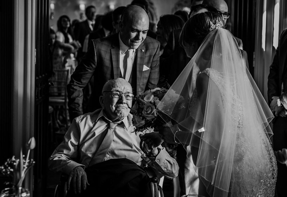 black and white photo of an emotional grandad first seeing the bride after the service