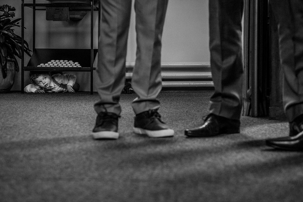 brides son hiding under a table as his mother walks into the church. Groomsmen shoes in the foreground waiting at the alter - black and white photo