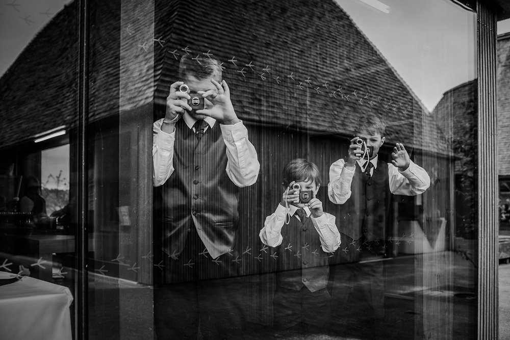 3 boys all filming through a window - black and white photo