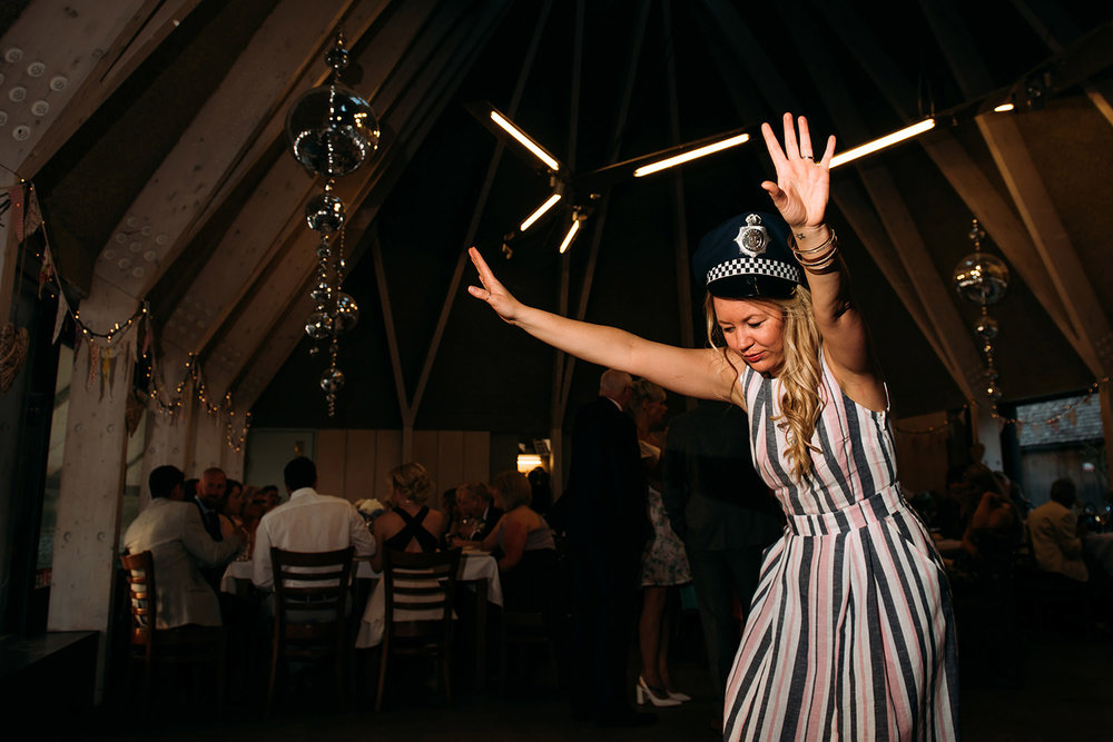 girl partying solo on the dance floor with a policeman's hat on