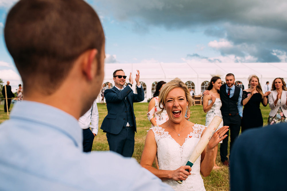 brides turn to bat during a game of rounders at the wedding