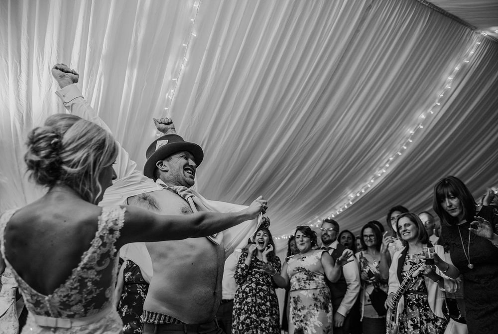 black and white photo of bride ripping open grooms shirt on the dancefloor