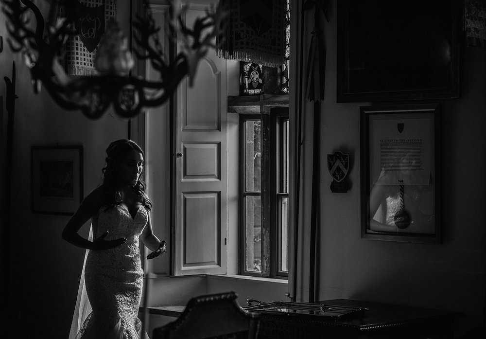 bride walking past a window taking nervous, big, calming breaths on the way to get married at Browsholme hall