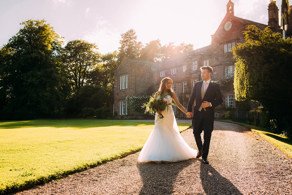 couple walking through nice light in front of Browsholme hall