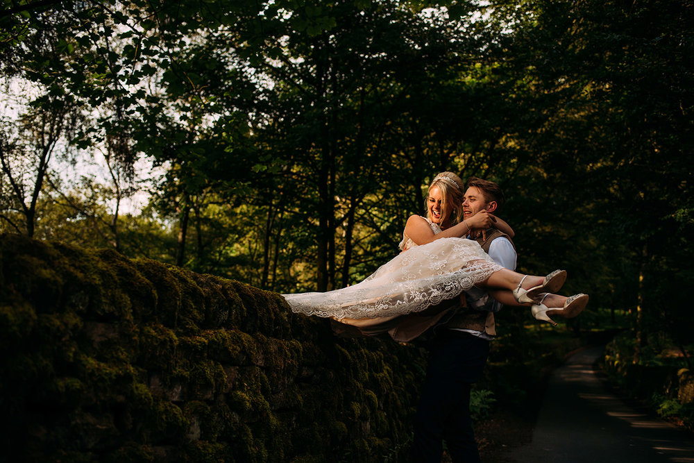 groom lifting bride over a wall