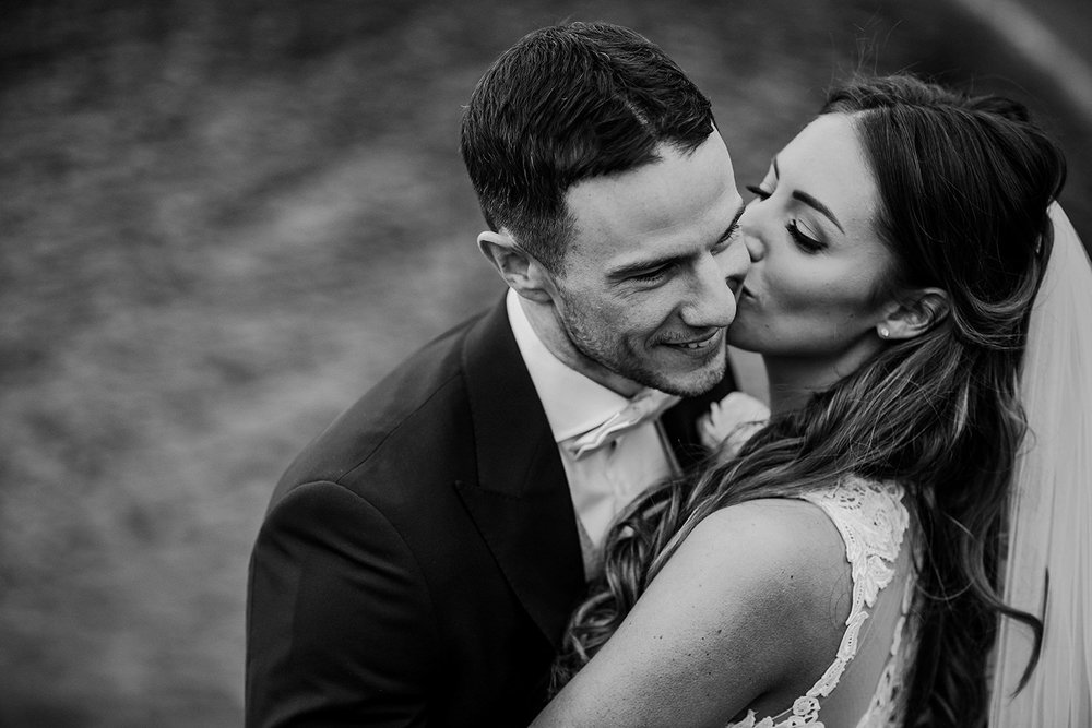 black and white photo of bride kissing the groom on the cheek