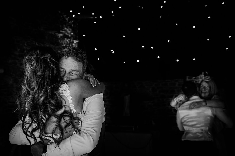 bw photo, bride hugging dad, groom hugging mum