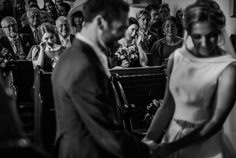 bw photo of 2 bridesmaids wiping tears from their eyes during the wedding vows