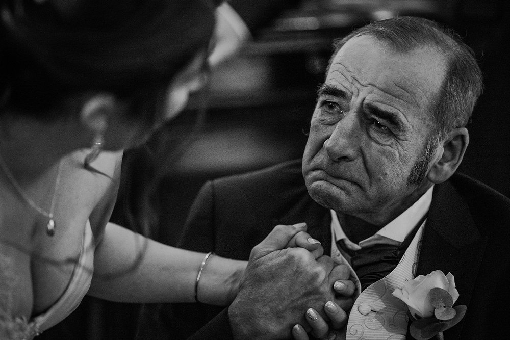 emotional father of the bride squeezing her hand and holding the tears back
