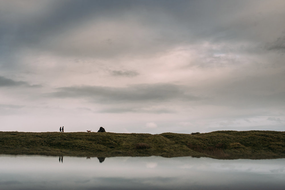 couple walking their dog in the distance on Pendle hill with reflection
