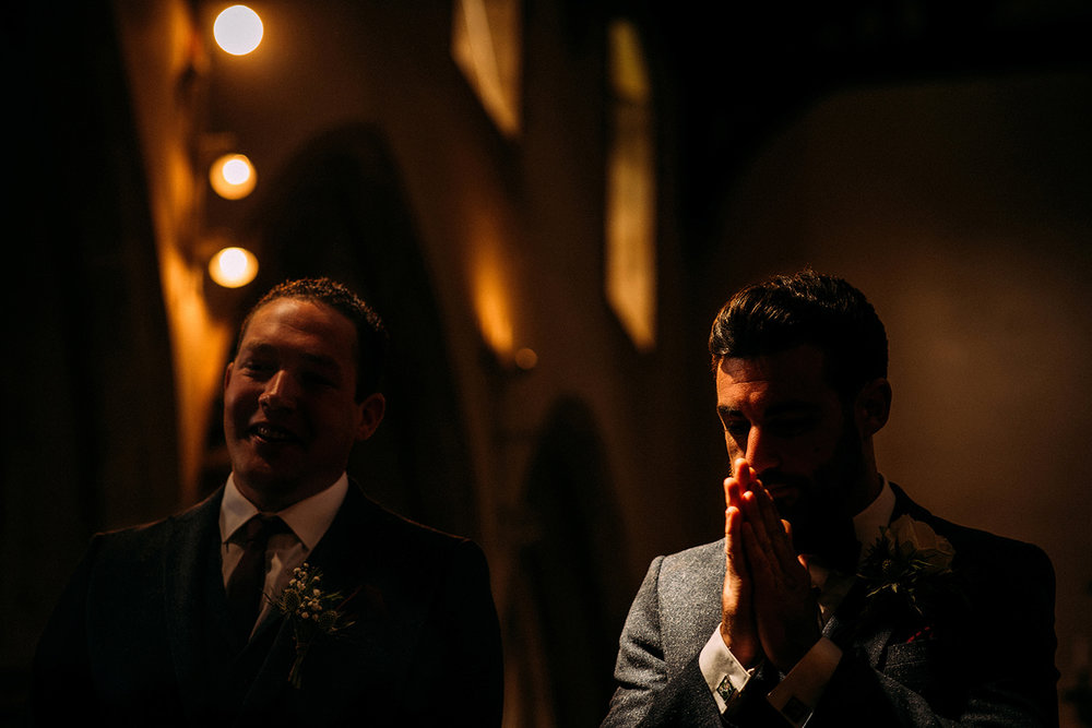 nervous groom at the alter in cool light