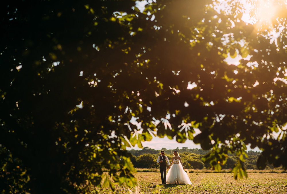 bride and groom walking through a field with nice sun light