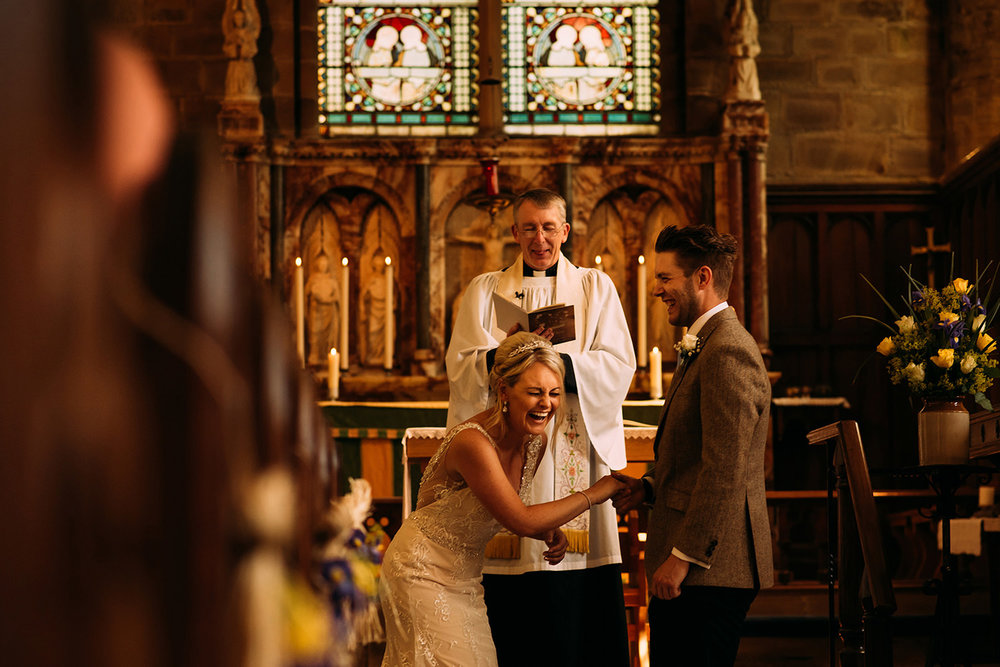 bride and groom laughing in church as the vicar got the words wrong