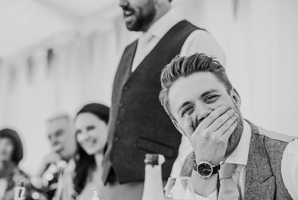embarrassed groom during best man speech - black and white photo