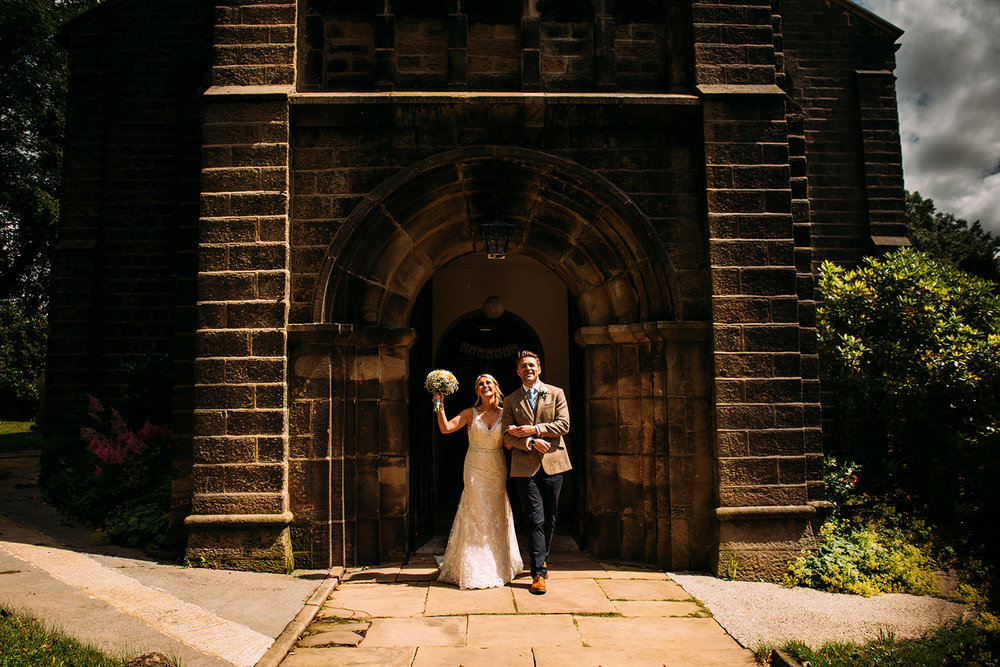 bride and groom leaving church very happy