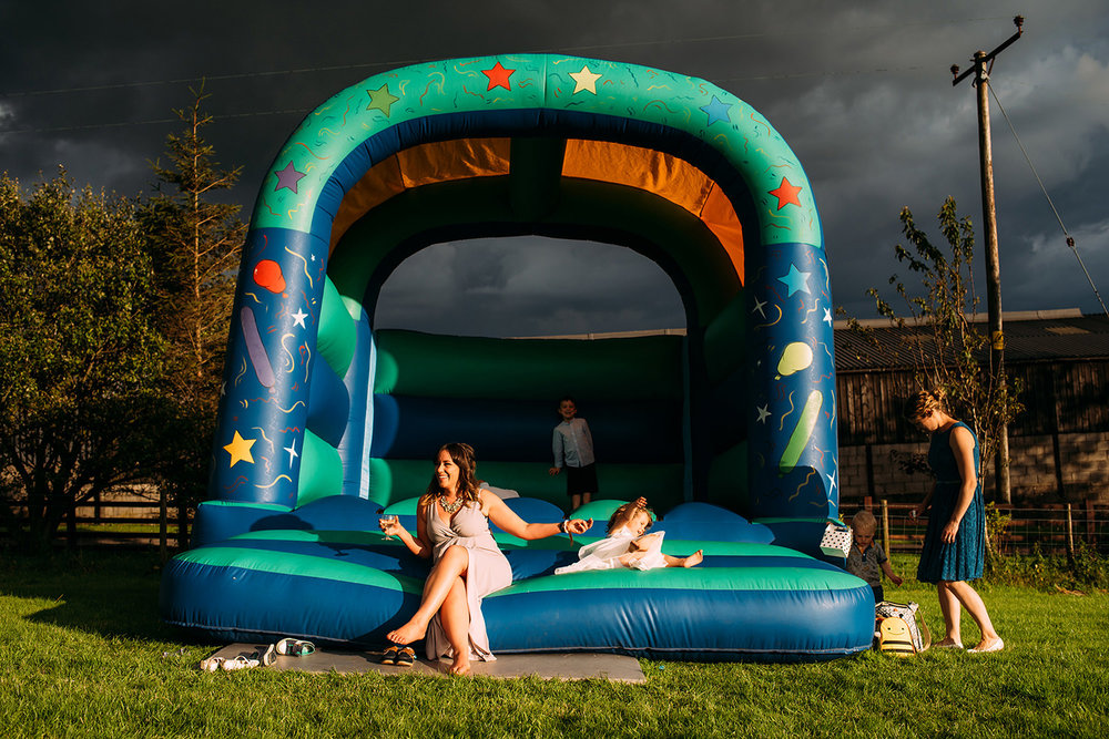 adult guest sat on bouncy castle as kids bounce around behind her