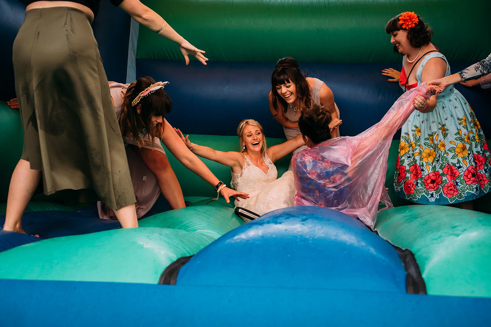 bride and friends falling on the bouncy castle