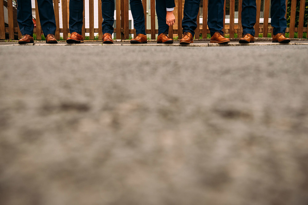 dead space of the road leading up to the groomsmen's shoes at the top of the frame