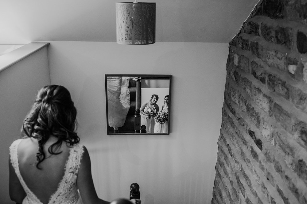 black and white photo of the bride walking down the stairs while her friends see her reflection in the mirror