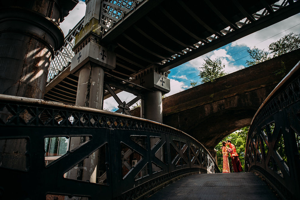 Bride and groom in traditional Chinese clothes under the bridges in Castlefield, Manchester