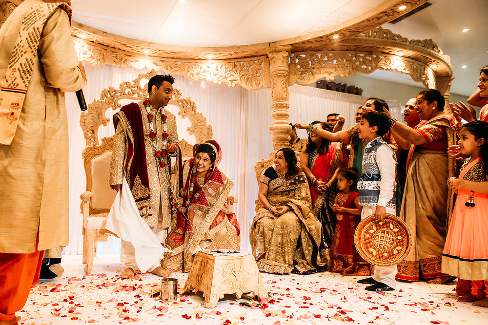 fun during Indian wedding celebrations, bride laughing, flower petals all over the floor