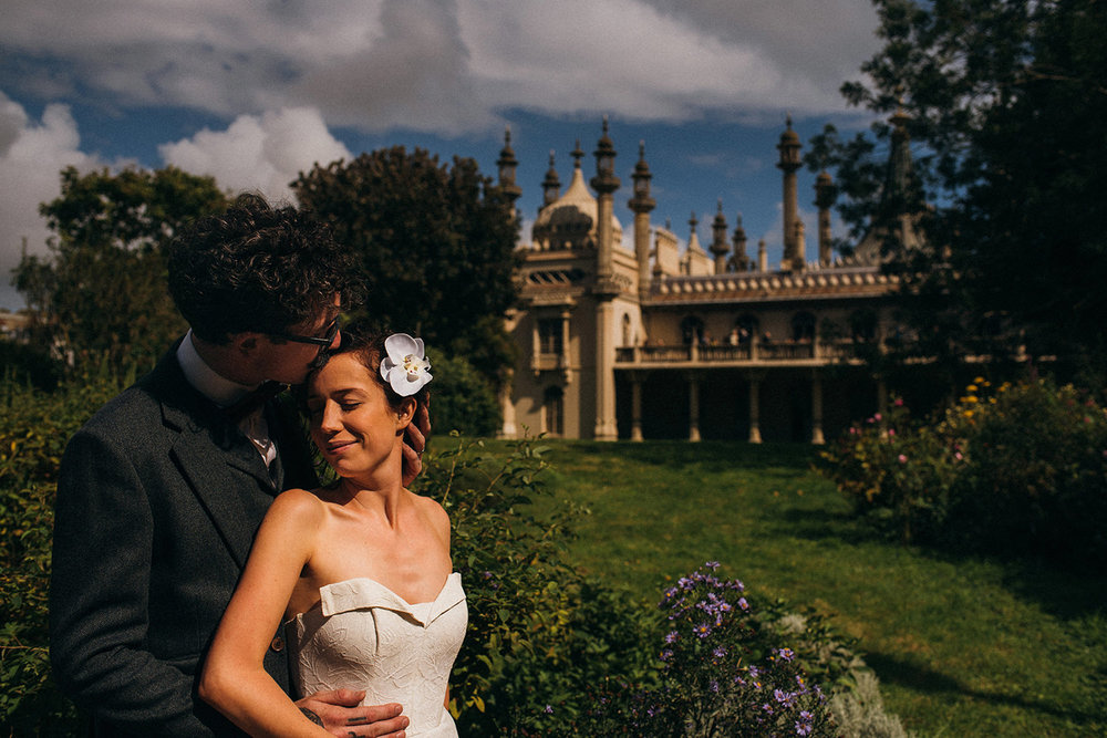 groom kissing bride's head in front of Brighton Pavilion