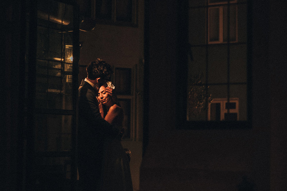 Bride and groom embracing by a light in the dark