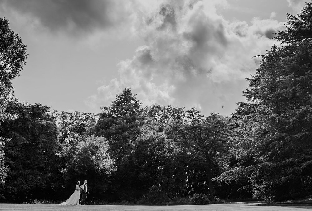 bride and groom walking through the grounds of Bartle hall