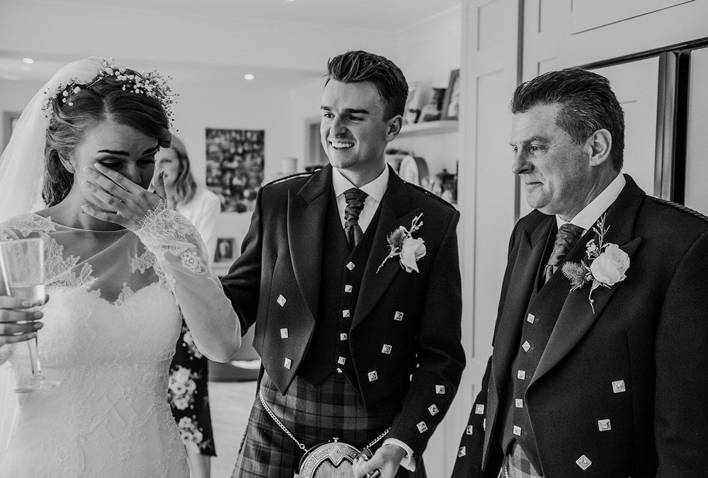 emotional bride with brother and father