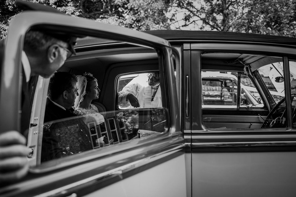 bw photo of bride and father in wedding car with driver and vicar looking in