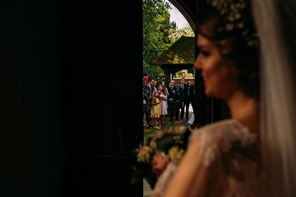 bride looking out of the church door about to walk through confetti