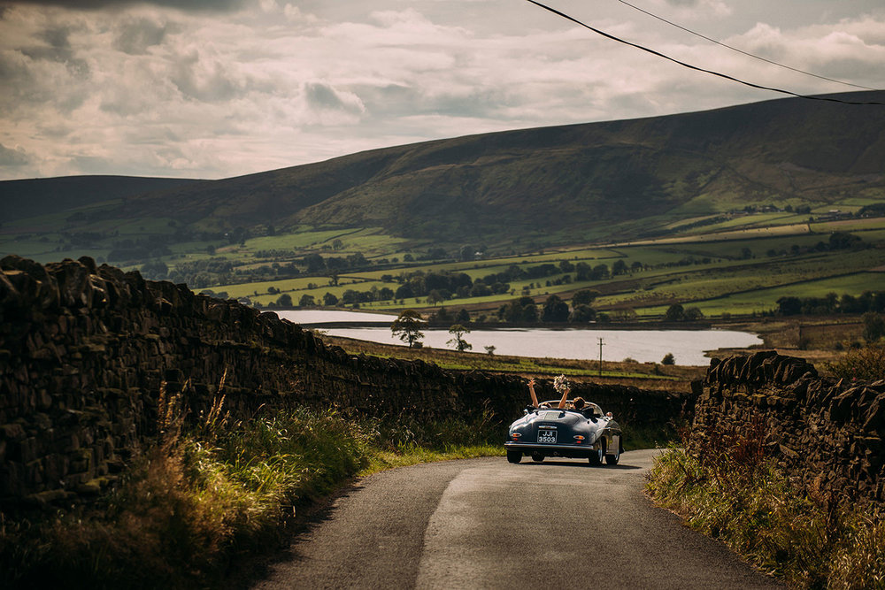 bride throws her arms up in the air as her and husband drive through stunning scenery in a classic Porsche