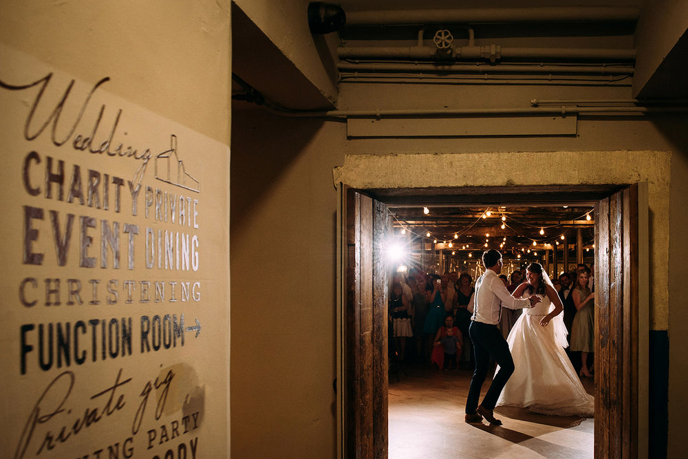 couple first dance through a door at Holmes mill