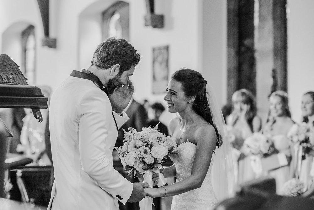 emotional groom during the church vows. Black and white photo