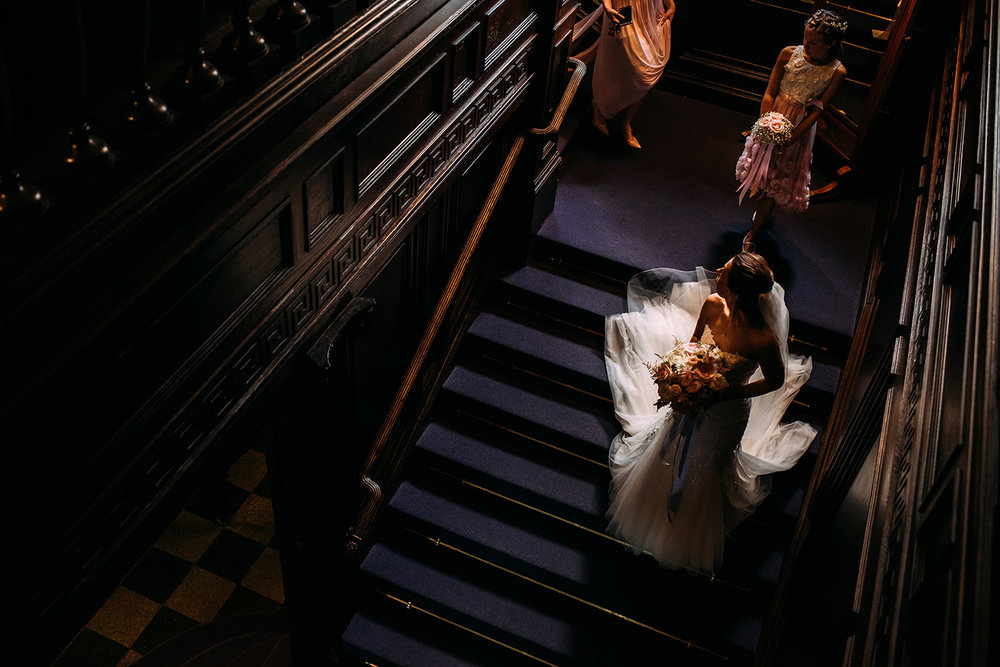 bride walking down the stairs followed by bridesmaids at Eaves hall