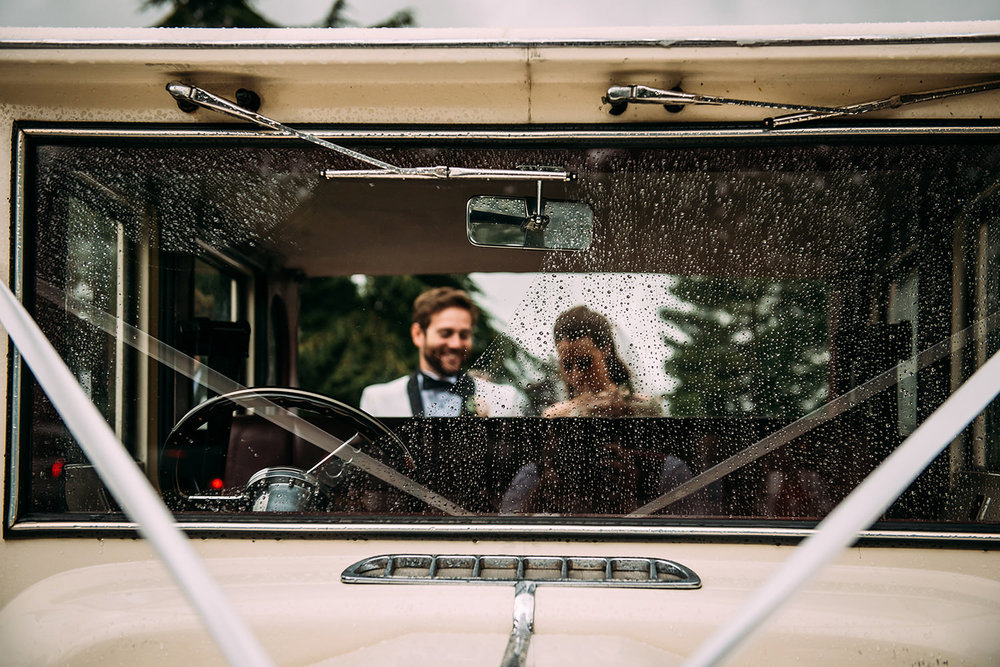 rain drops on the bridal car, couple in the background
