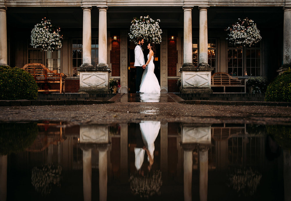 Bride and groom at the front of Eaves hall with a big puddle reflection